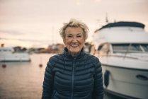 Портрет счастливой пожилой женщины, стоящей в гавани во время заката — стоковое фото