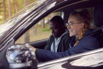Femme souriante, volant de voiture assis avec homme — Photo de stock