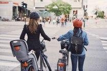 Vista posteriore delle donne con biciclette che attraversano la strada in città — Foto stock