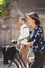 Vista lateral de pessoas de negócios andando com bicicletas na rua — Fotografia de Stock