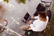 Висока кут зору бізнесмена, використовуючи ноутбук, сидячи на лавці в парку — стокове фото