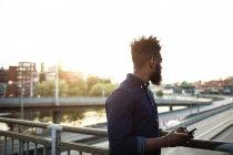 Jeune homme avec téléphone portable debout sur le pont contre le ciel — Photo de stock