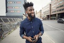 Homme heureux avec téléphone portable tout en marchant sur le trottoir tout en regardant loin dans la ville — Photo de stock