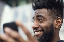 Vue à angle bas de l'homme heureux en utilisant le téléphone mobile — Photo de stock