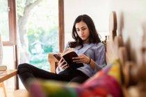 Adolescente leitura livro menina enquanto sentado no sofá — Fotografia de Stock