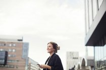 Low angle view of happy woman holding mobile phone while standing in city — Stock Photo