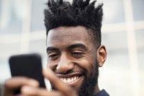 Vista de ángulo bajo de hombre feliz con teléfono inteligente - foto de stock