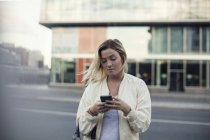 Young woman using mobile phone against building in city — Stock Photo