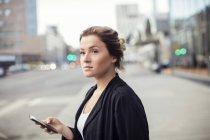 Mujer sosteniendo teléfono móvil mientras está de pie en la ciudad - foto de stock
