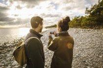 Hombre buscando a mujer fotografiando mar cielo de teléfono móvil en la playa - foto de stock