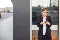 Giovane donna che ascolta musica contro la finestra di vetro in città — Foto stock