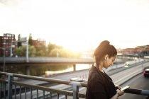 Vista laterale della donna che utilizza il telefono cellulare mentre sul ponte in piedi contro il cielo — Foto stock