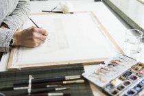 Vista laterale della mano femminile con pennello e acquerelli — Foto stock