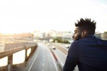 Visão traseira do homem de pé na ponte sobre a rua da cidade contra o céu — Fotografia de Stock