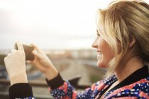 Vista lateral de la mujer fotografiando desde el teléfono móvil - foto de stock
