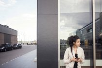 Молода жінка, використовуючи смарт-телефон під час фотографіях хтось дивитися вбік від вікна — стокове фото