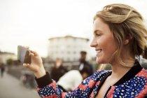 Vista lateral de la mujer feliz fotografiando desde el teléfono inteligente - foto de stock