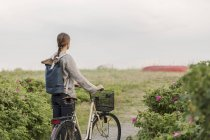 Vue arrière de la femme qui marche avec la bicyclette sur le sentier au milieu des plantes contre le ciel clair — Photo de stock