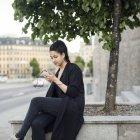 Молода жінка, використовуючи смарт-телефон, сидячи на підпірної стінки в місті — стокове фото