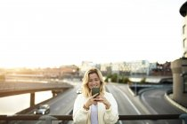Happy young woman using mobile phone while standing on bridge against sky — Stock Photo