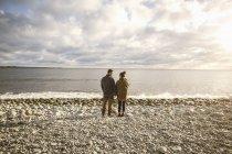 Vista posterior de la situación de pareja en la costa rocosa en la playa contra el cielo - foto de stock