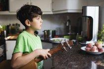 Задумчивый мальчик, держащий гитару, стоя у кухонного стола — стоковое фото