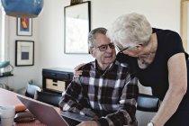 Sonriente pareja senior con laptop en mesa de comedor - foto de stock