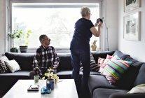 Старший мужчина смотрит на женщину, поправляющую пол за диваном в гостиной — стоковое фото