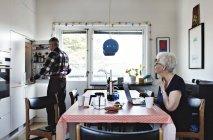 Старший женщина, сидя за обеденным столом, а мужчина стоял холодильник на кухне — стоковое фото
