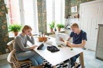 Мальчик-подросток шьет текстиль в то время как девочка-подросток использует цифровой планшет дома — стоковое фото