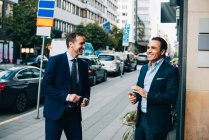 Cheerful mature male business coworkers talking while standing on sidewalk in city — Stock Photo