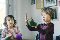 Menino que olha o amigo que gesticula na casa — Fotografia de Stock