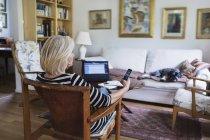 Donna anziana che utilizza smartphone a casa mentre il cane si rilassa sul divano — Foto stock