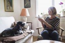 Senior mulher fotografar cão através de telefone inteligente em casa — Fotografia de Stock