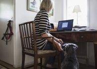 Собака сидит со старшей женщиной, используя ноутбук дома — стоковое фото