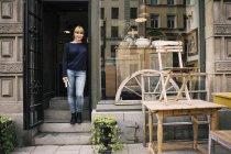 Proprietária feminina em pé na entrada da loja de antiguidades — Fotografia de Stock