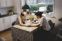 Лесбиянки используют цифровые планшеты, держа за руки за обеденный стол — стоковое фото