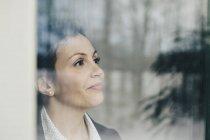 Gros plan d'une femme d'affaires réfléchie vue à travers une vitre au bureau — Photo de stock