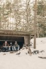 Friends sitting in log cabin against trees during winter — Stock Photo