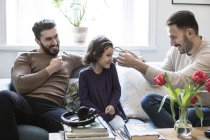 Father is making daughter wear eyeglasses while sitting with partner on sofa at home — Foto stock