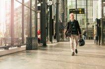 Comprimento total de viajante masculino sênior, andando com a bagagem na estação de trem — Fotografia de Stock