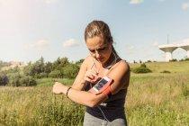 Жінка, що використання мобільного телефону на руки смуги при здійсненні трава проти неба — стокове фото