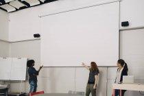 Técnicos multi-étnicos confiantes dando apresentação sobre tela de projeção em branco no escritório criativo — Fotografia de Stock