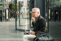 Senior male commuter talking through earphones while sitting by bags at railroad station — Stock Photo