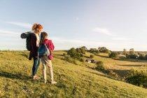 Comprimento total de mãe e filha com mochilas em pé na colina contra o céu durante o pôr do sol — Fotografia de Stock