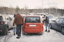 Amigos, caminhando para o carro no estacionamento durante o inverno — Fotografia de Stock