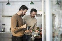 Pareja gay que prepara comida en casa en la cocina - foto de stock