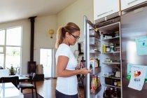 Вид сбоку женщины с помощью мобильного телефона стоя, открыть холодильник на кухне — стоковое фото