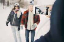 Woman photographing friends through smart phone on field during winter — Stock Photo