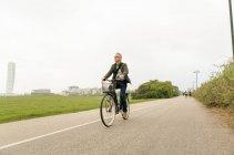 Longitud total de senior masculino viajero ciclismo en carretera contra el cielo claro - foto de stock